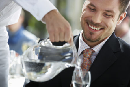 Waiter Pouring Man's Water --- Image by © Royalty-Free/Corbis